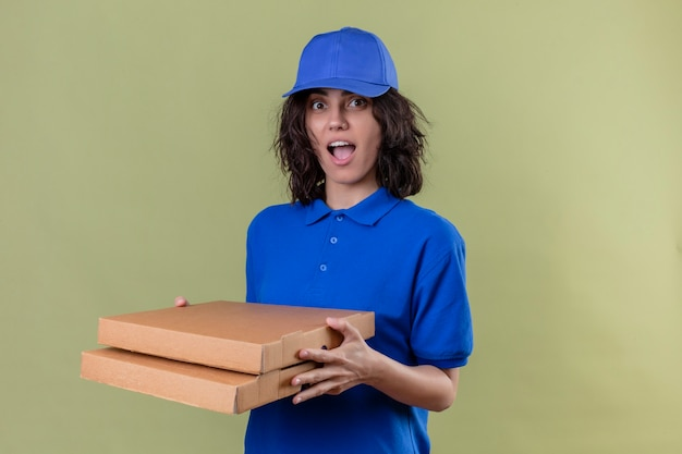 Delivery girl in blue uniform and cap holding pizza boxes looking joyful positive and happy smiling cheerfully standing over isolated green space