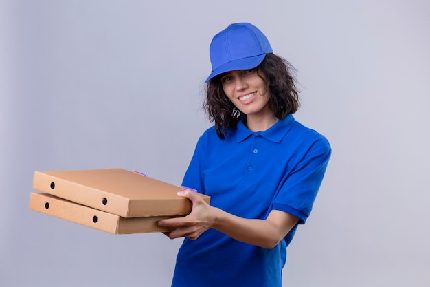 Delivery girl in blue uniform and cap holding pizza boxes looking joyful positive and happy smiling cheerfully standing over isolated white space