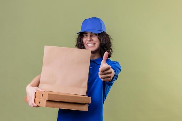 Ragazza delle consegne in uniforme blu e cappuccio che tiene le scatole della pizza e il pacchetto di carta che sorride allegramente mostrando i pollici in su in piedi sopra lo spazio verde isolato