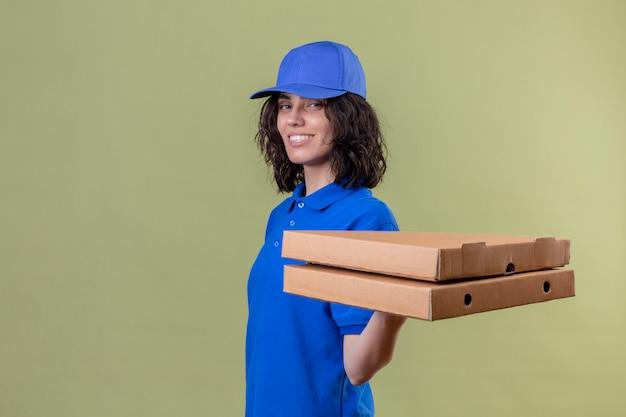 Ragazza delle consegne in uniforme blu e cappuccio che tiene le scatole per pizza in piedi amichevole sorridente positivo e felice sul verde isolato