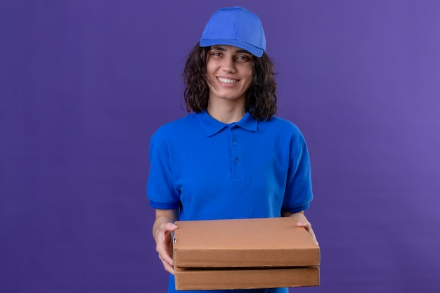 Delivery girl in blue uniform and cap holding pizza boxes positive and happy smiling friendly standing on isolated purple