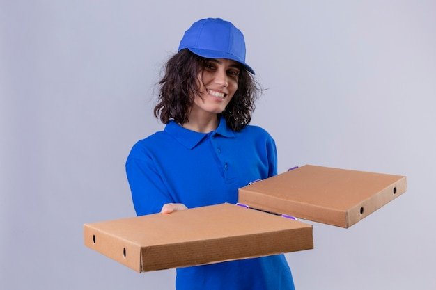 Delivery girl in blue uniform and cap holding pizza boxes  positive and happy smiling friendly standing over isolated white space