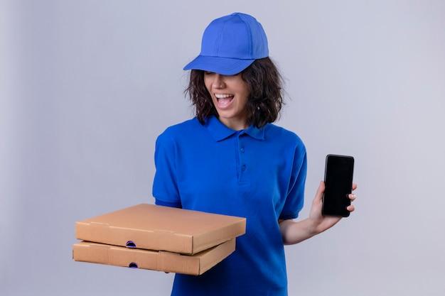 Ragazza delle consegne in uniforme blu e cappuccio che tengono le scatole per pizza sorridendo allegramente mostrando il telefono cellulare in piedi sul bianco
