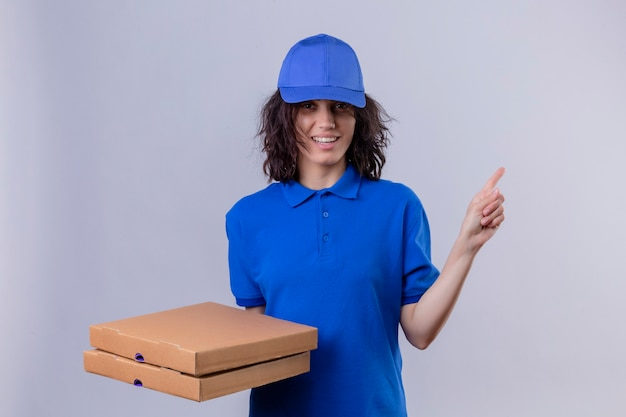 Delivery girl in blue uniform and cap holding pizza boxes  smiling friendly pointing with index finger to the side standing over isolated white space