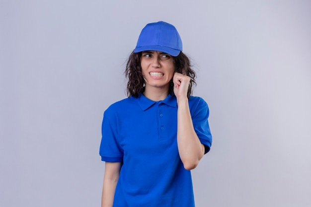Delivery girl in blue uniform and cap looking confused and frustrated standing over isolated white space