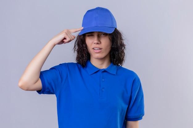 Ragazza delle consegne in uniforme blu e cappuccio che punta il tempio con il pensiero del dito concentrato su un compito in piedi