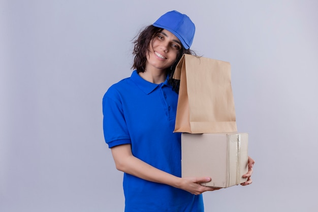 Delivery girl in blue uniform and cap smiling friendly hugging cardboard boxes standing on white