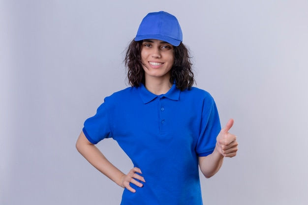 Delivery girl in blue uniform and cap smiling friendly showing success , showing thumbs up standing on white