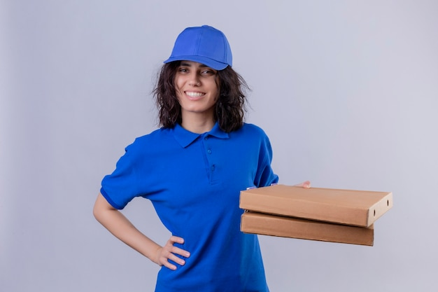 Delivery girl in blue uniform holding pizza boxes  positive and happy smiling friendly standing over isolated white space