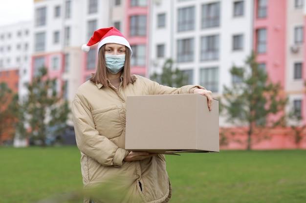 Доставщица в красной шляпе санта-клауса и медицинской защитной маске держит большую коробку на открытом воздухе. доставка в интернет-магазин в карантинное время. сервисный коронавирус.