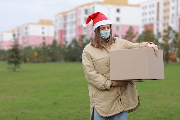Доставщица в красной шляпе санта-клауса и медицинской защитной маске держит большую коробку на открытом воздухе. доставка в интернет-магазин в карантинное время.