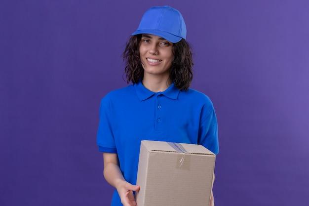 Доставщица в синей форме и кепке, держащая коробку, улыбается дружелюбно, позитивно и счастливо, стоя на изолированном фиолетовом