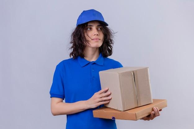 Доставщица в синей форме и кепке держит коробки с пакетами, глядя в сторону с серьезным и уверенным выражением лица.