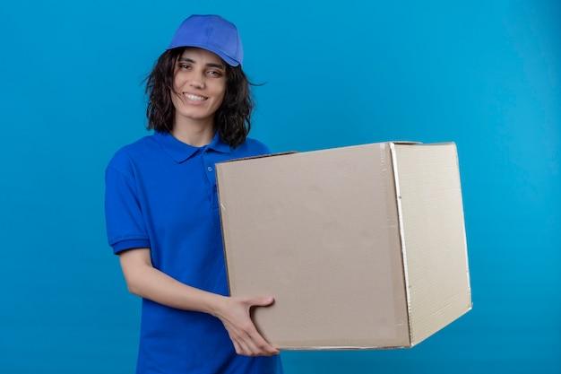 Доставщица в синей форме и кепке держит большую картонную коробку с улыбкой на лице, позитивно и счастливо стоя на синем