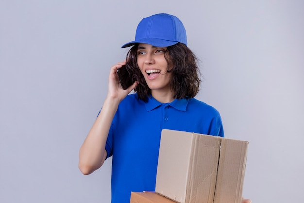 Доставщица в синей форме и кепке держит коробки для пиццы и коробку и разговаривает по мобильному телефону со счастливым лицом, стоящим на белом