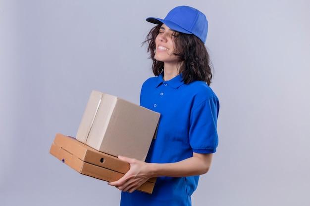 Доставщица в синей форме и кепке держит коробки для пиццы и коробку, стоя с закрытыми глазами с счастливым лицом, улыбаясь, стоя на белом