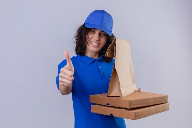 Доставщица в синей форме и кепке держит коробки для пиццы и бумажный пакет с улыбкой на лице, показывая большие пальцы руки вверх, стоя на белом