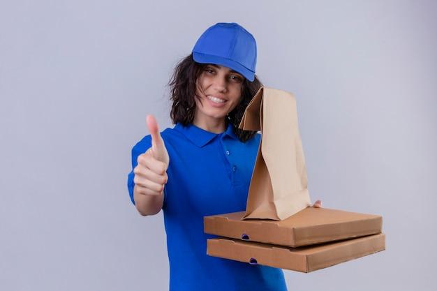 Доставщица в синей форме и кепке держит коробки для пиццы и бумажный пакет с улыбкой на лице, показывая большие пальцы вверх стоя