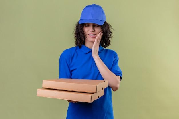 Доставщица в синей форме и кепке держит коробки для пиццы, кусая губу с голодным выражением лица, улыбаясь, стоя на изолированном оливковом цвете