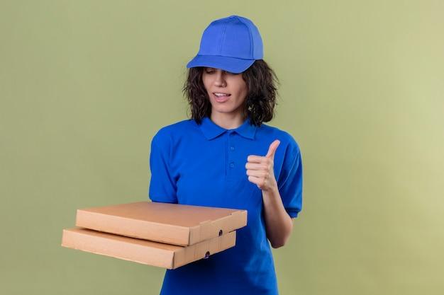 Доставщица в синей форме и кепке держит коробки для пиццы, глядя вниз, показывая пальцы вверх, улыбаясь уверенно, стоя на оливковом цвете