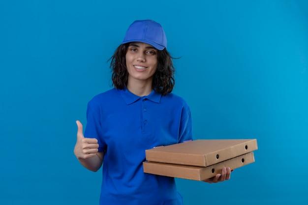 Доставщица в синей форме и кепке держит коробки для пиццы с улыбкой на лице, показывая пальцы вверх, стоя на синем
