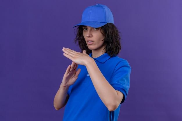 Доставщица в синей форме и кепке смотрит на работу, делая жест тайм-аута руками на изолированном фиолетовом