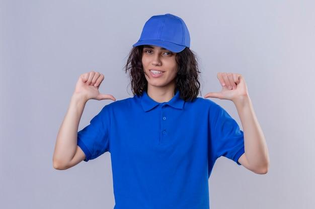 Доставщица в синей форме и кепке указывает на себя, выглядит уверенно, улыбается, самодовольно и гордо стоит