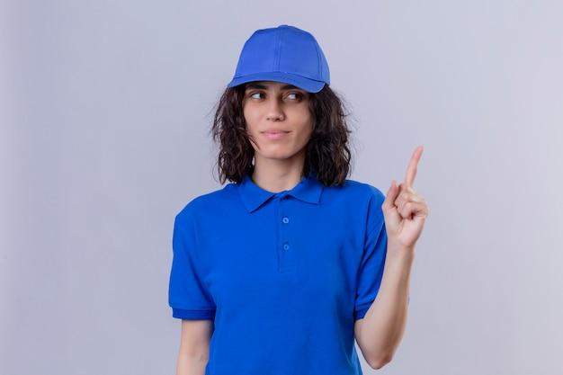 Доставщица в синей форме и кепке, указывая пальцем, уверенно улыбаясь, сосредоточилась на задаче, стоя на белом