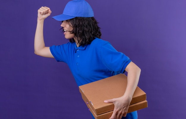 Доставщица в синей униформе и кепке спешит доставлять коробки для пиццы покупателю над фиолетовым пространством