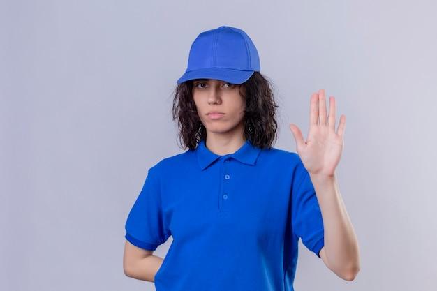 Доставщица в синей форме и кепке стоит с открытой рукой, делая знак остановки с серьезным и уверенным жестом защиты