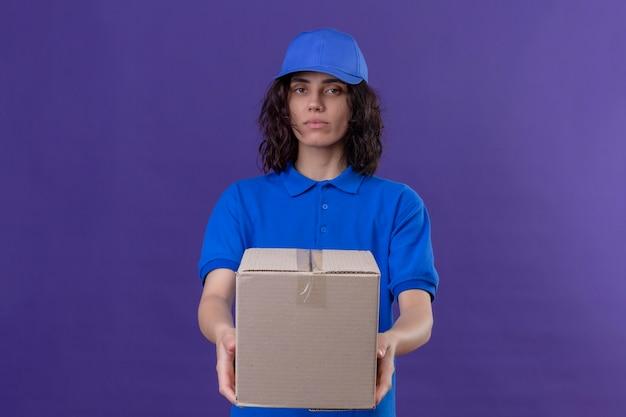 青い制服を着た配達の少女と深刻な自信を持って立っているボックスパッケージをストレッチキャップ