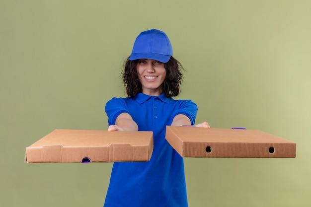 Доставщица в синей униформе и кепке протягивает коробки для пиццы, дружелюбно улыбаясь, со счастливым лицом, стоящим на изолированном оливковом цвете