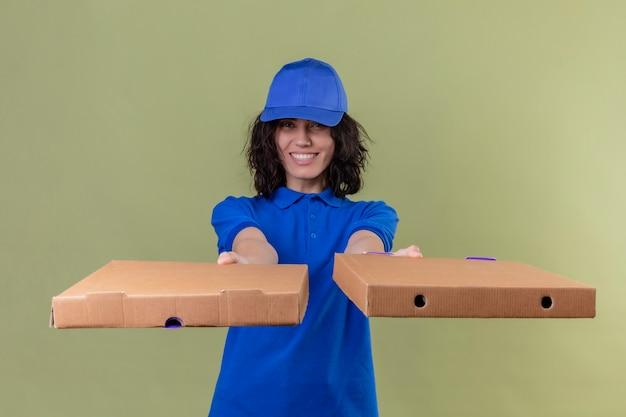 青い制服を着た配達の女の子とピザボックスを分離したオリーブ色のスペースの上に立って幸せそうな顔でフレンドリーな笑顔のピザボックス