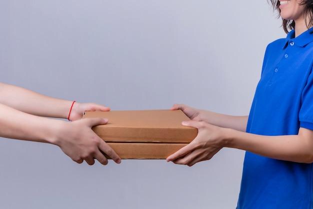 孤立した白いスペースの上のuの顧客にピザの箱を与える青い制服を着た配達の少女