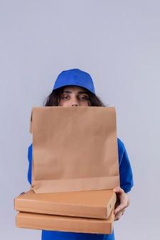 Доставщик в синей форме прячется за коробками для пиццы и стоящим бумажным пакетом