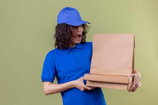 Доставщица в синей форме держит коробки для пиццы и бумажный пакет, выглядя удивленными и счастливыми, стоя над зелеными насаждениями