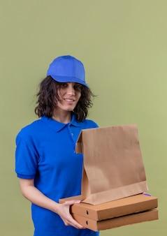 Доставщица в синей форме держит коробки для пиццы и бумажный пакет, уверенно улыбаясь, стоя на изолированном зеленом