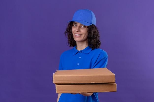Доставщица в синей форме держит коробки для пиццы позитивными и счастливыми, улыбающимися, дружелюбными, стоя на изолированном фиолетовом