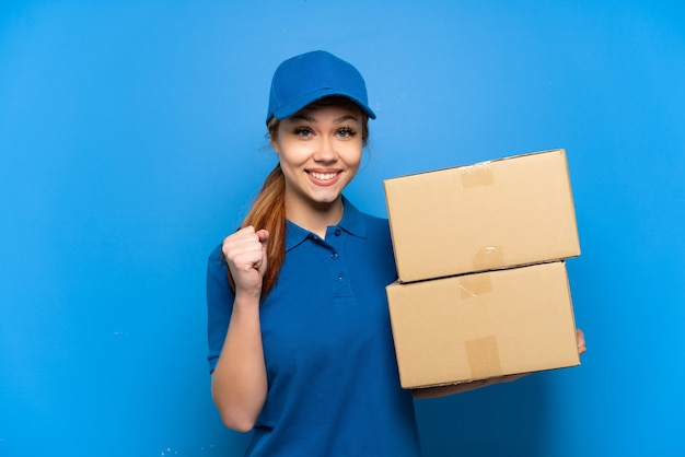 Delivery girl over isolated blue wall celebrating a victory in winner position