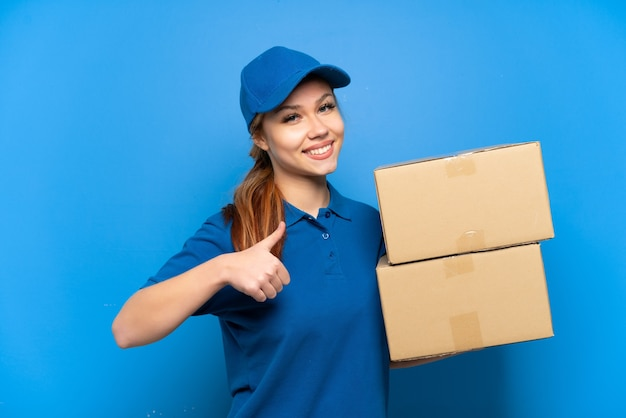 Delivery girl over isolated blue wall giving a thumbs up gesture