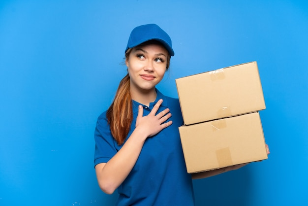 Delivery girl over isolated blue wall looking up while smiling
