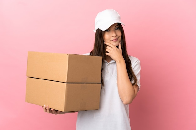Delivery girl over isolated pink wall thinking