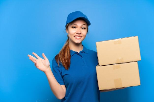 孤立した青い壁の上の配達の女の子は、来るように誘うために手を横に伸ばします