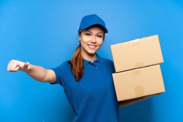 Доставщица над изолированной синей стеной, показывая большой палец вверх