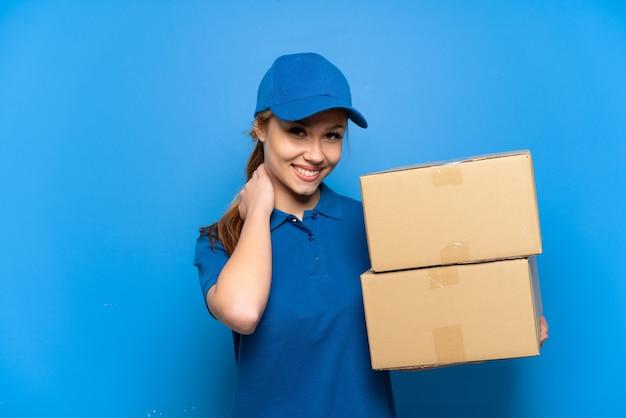 Доставка девушка над изолированной синей стеной смеется