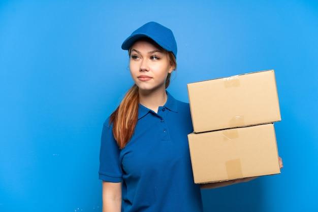 Доставка девушка над изолированной синей стеной, глядя в сторону
