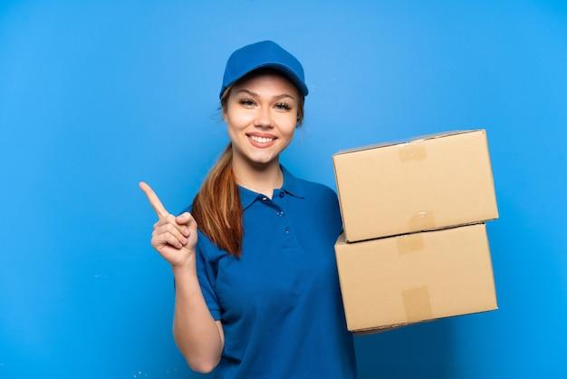 Доставщица над изолированной синей стеной, указывая в сторону, чтобы представить продукт