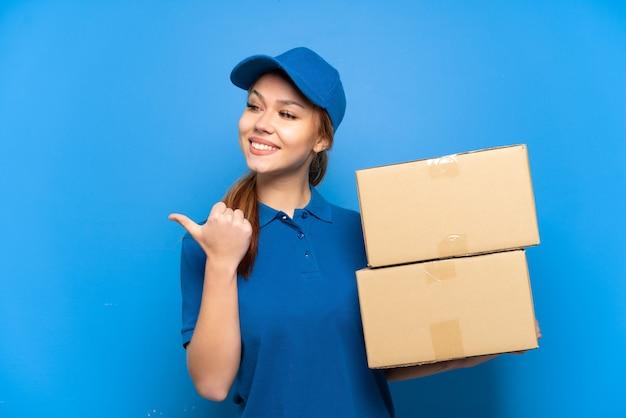 제품을 제시하기 위해 측면을 가리키는 격리 된 파란색 벽 위에 배달 소녀