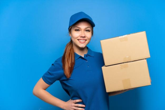 Доставка девушка над изолированной синей стеной позирует с руками на бедрах и улыбается