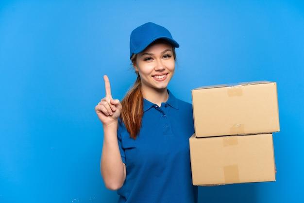 Доставщица над изолированной синей стеной показывает и поднимает палец в знак лучших